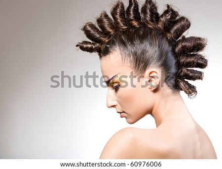 studio portrait of young beautiful brunette with creative makeup and hairstyle - stock photo