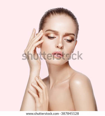 Studio portrait of young beautiful model with hand near her face on pink background. Perfect fresh clean skin. Professional makeup. Brunette hair. Hands touching her face. Not isolated - stock photo