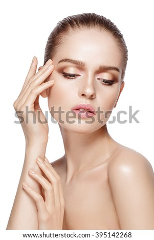 Studio portrait of young beautiful model with professional makeup on white background. Perfect fresh clean skin. Deep blue eyes. Brunette hair. Hands touching her face. Isolated - stock photo