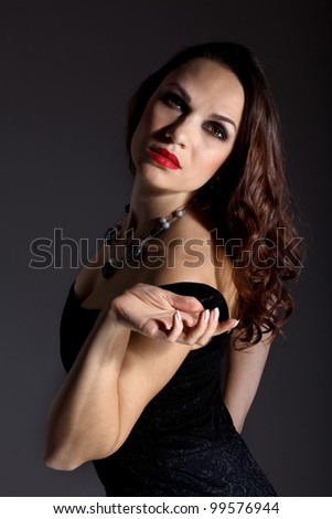 Studio portrait of young beautiful woman against black background