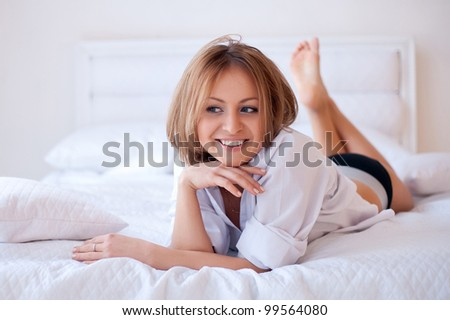 Studio portrait of young beautiful woman on bed - stock photo