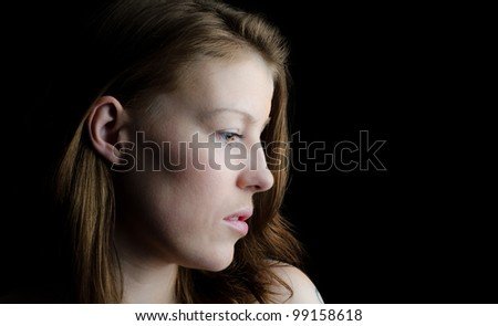 Studio portrait of young beautiful woman with a thoughtful expression - stock photo