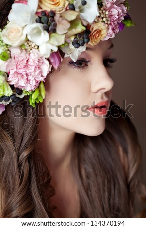 Studio portrait of young beautiful woman with flowers in hair
