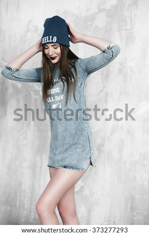 Studio portrait of young cute girl in grey dress and blue hat with purple lips makeup