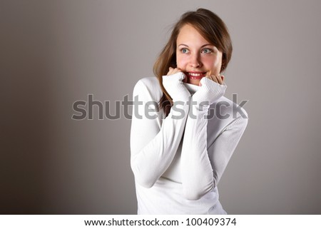 Studio portrait of young girl in white sweater - stock photo