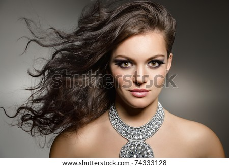 studio portrait of young gorgeous brunette with evening make up