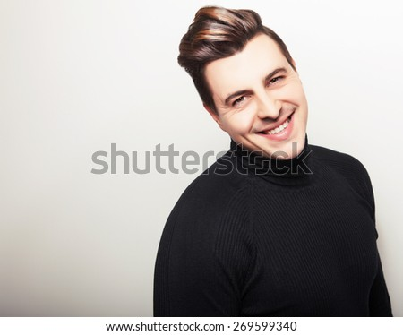 Studio portrait of young handsome man in black knitted sweater. Close-up photo.  - stock photo