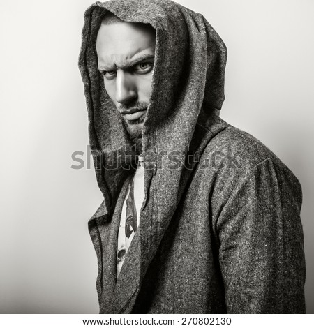 Studio portrait of young handsome man in casual cape with a hood. Close-up sepia photo.  - stock photo
