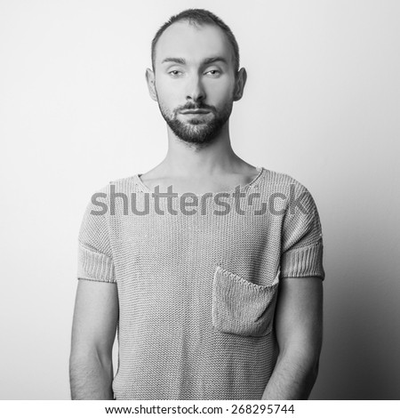 Studio portrait of young handsome man in casual knitted sweater. Black-white close-up photo.  - stock photo
