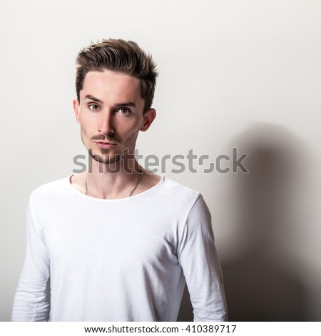 Studio portrait of young handsome man in casual simple white t-shirt.