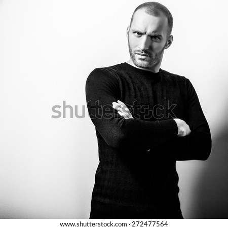 Studio portrait of young handsome man in knitted sweater. Black-white close-up photo.