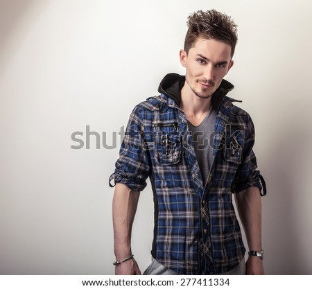 Studio portrait of young handsome man in stylish dark blue jacket.  - stock photo