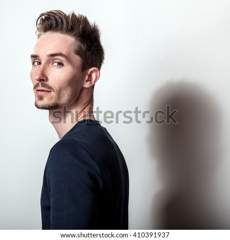 Studio portrait of young handsome man in stylish dark blue t-shirt.