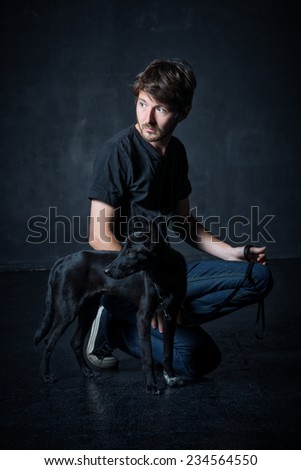 studio portrait of young man and his black dog