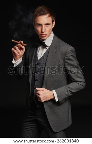 Studio portrait of young man smoking a cigar - stock photo