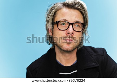 Studio portrait of young man with long blond hair wearing glasses and black jacket. Isolated on light blue background.