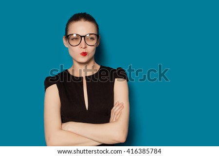 Studio Portrait of young pretty thoughtful criticizing female. Colorful blue background, isolated - stock photo