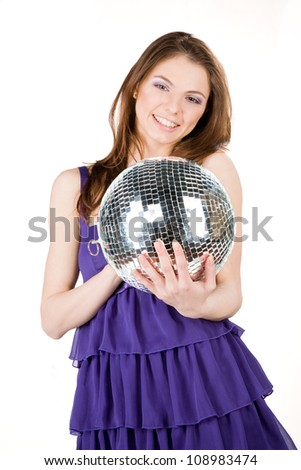Studio portrait of young woman in party dress holding disco ball - stock photo