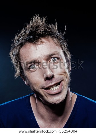 studio portrait on black background of a funny expressive caucasian man grimacing toothy smile - stock photo