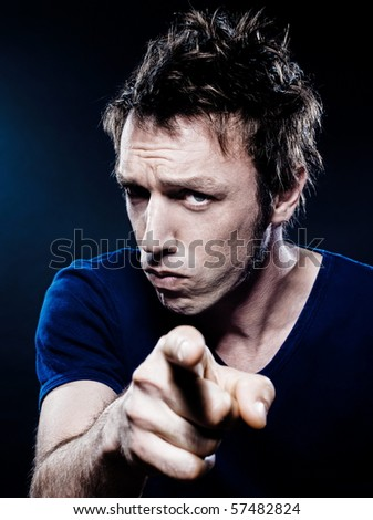 studio portrait on black background of a funny expressive caucasian man pointing menace - stock photo
