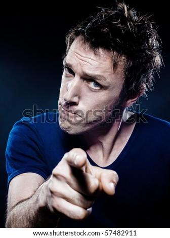 studio portrait on black background of a funny expressive caucasian man pointing menace suspicious - stock photo