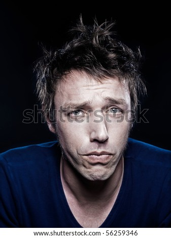 studio portrait on black background of a funny expressive caucasian man puckering sad upse