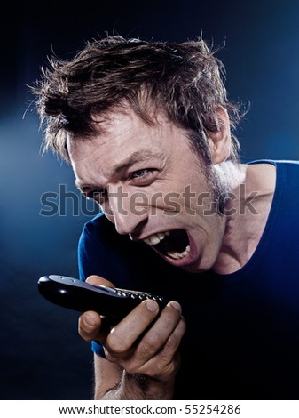 studio portrait on black background of a funny expressive caucasian man yelling at phone - stock photo