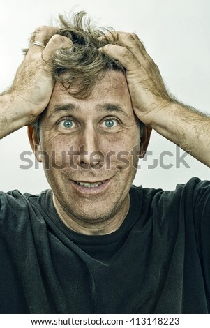 Studio portraitr of a man with his hands in his hair looking uneasy.