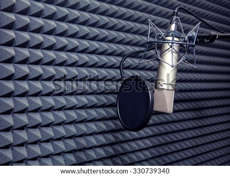 Studio recording microphone near wall with acoustic dampening foam - stock photo