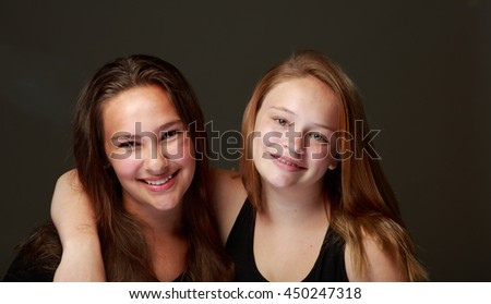 Studio set of two young teenage girls posing on a grey background