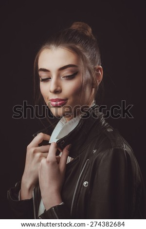 Studio shoot of beautiful woman with bright makeup and creative hairstyle in leather jacket