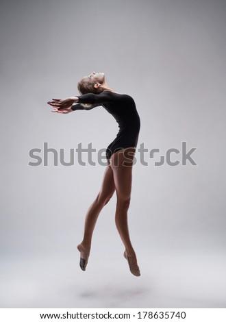 studio shoot of cute woman gymnast on grey studio background - stock photo