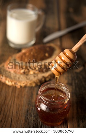 Studio shoot of Jar of honey and honey dipper, bread and knife, milk on wooden background