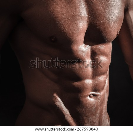 studio shoot of strong athletic man on dark background - stock photo