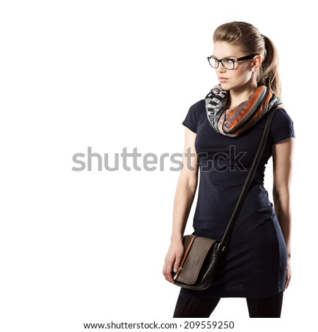Studio shoot of young attractive slim female fashion model wearing casual dress with leather handbag. Blonde fashionable woman in eyeglasses looking aside.   - stock photo