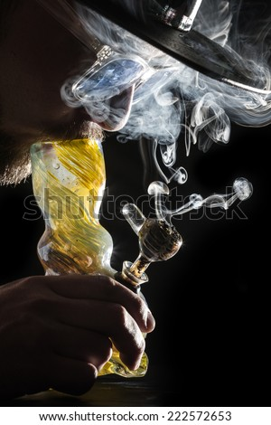 studio shoot with model simulating smoking pot through a bong in a dark high contrast image