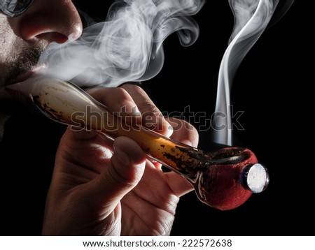 studio shoot with model simulating smoking pot with a pipe in a dark high contrast image