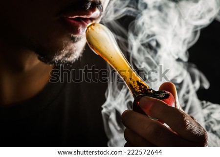 studio shoot with model simulating smoking pot with a pipe in a dark high contrast image - stock photo