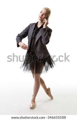 Studio shot af a ballerina model holding a phone to her left ear. - stock photo