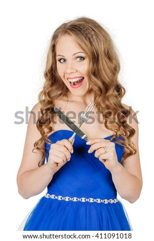 Studio shot beautiful young girl in elegant blue dress with fork and knife and looking at the camera. image on a white studio background. - stock photo