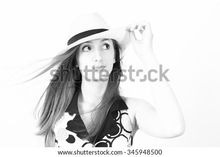 Studio shot black and White of a young woman with a cocky expression.  Her hair blows as she holds the brim of her hat. - stock photo