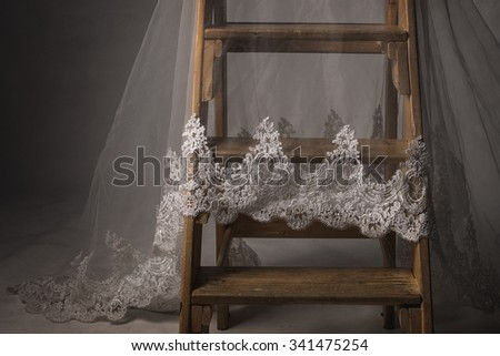Studio shot low key photography of wooden ladder covered with bridal veil
