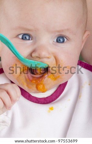 studio shot of a baby girl eating her first mashed carrot. mother feeding her baby girl with  mashed carrots - stock photo