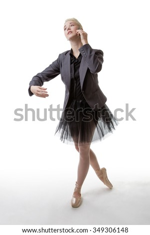 Studio shot of a ballerina model holding a phone to her left ear, with her right arm poised infront of her - stock photo
