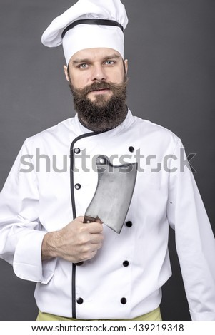 Studio shot of a  bearded chef  holding a butcher knife over gray background - stock photo
