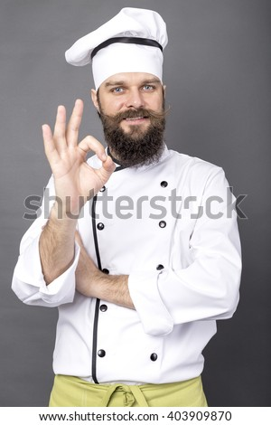 Studio shot of a bearded chef showing OK sign over gray background