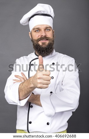 Studio shot of a bearded chef with thumb up over gray background