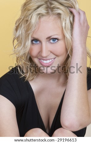 Studio shot of a beautiful blond haired blue eyed female model looking happy