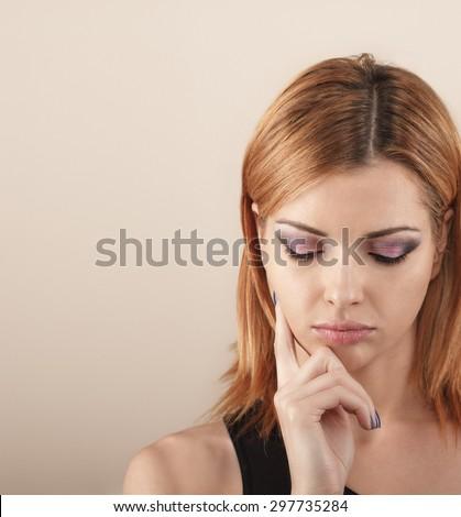 Studio shot of a beautiful pensive young woman. - stock photo