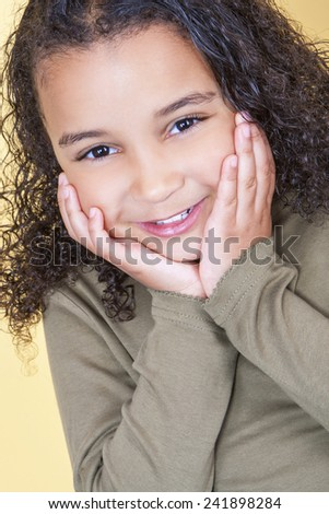 Studio shot of a beautiful young mixed race African American girl smiling and looking cheeky with hands on her face - stock photo